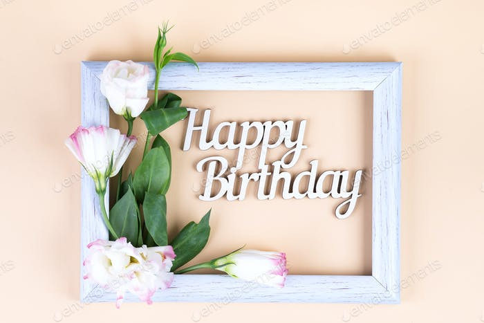 Empty white frame and flowers eustoma on beige paper background with copy space. Birthday concept
