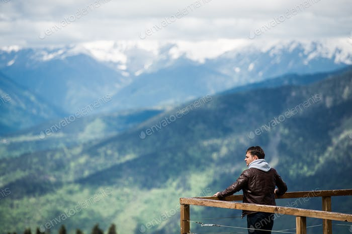 Man on a desk in mountains observing the landscape