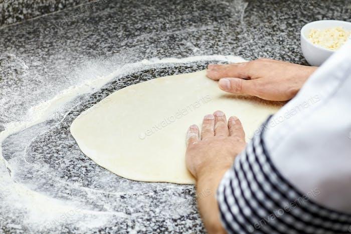 Kneading pizza dough.