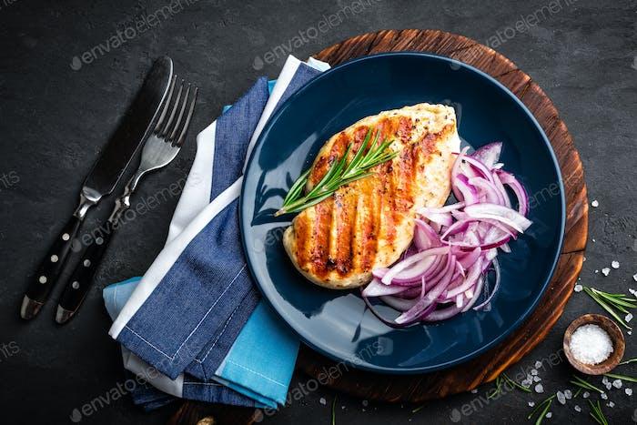 Jugosa carne de pollo a la parrilla, filete con cebolla marinada fresca en el plato. Fondo negro, vista superior