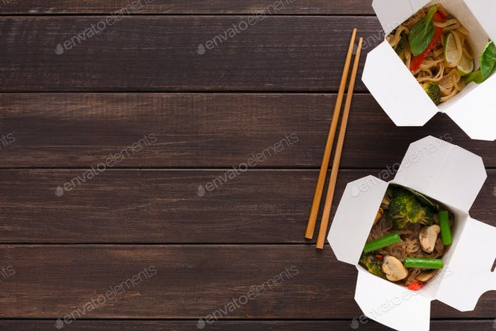 Asian food in delivery box on wooden backgorund