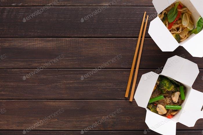 Asiatische Lebensmittel in Lieferbox auf Holzbackgorund