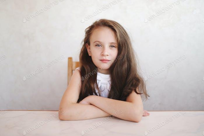 kleines Mädchen sitzt am Tisch