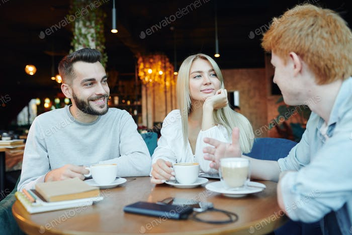 Happy young heterosexual couple chatting to their friend by cup of cappuccino