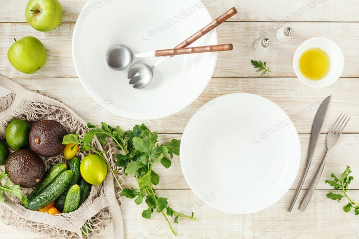 Empty bowls and ingredients for making a salad