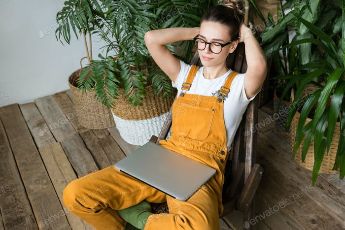 Woman gardener closed eyes put hands behind head resting after work, sitting on chair in home garden