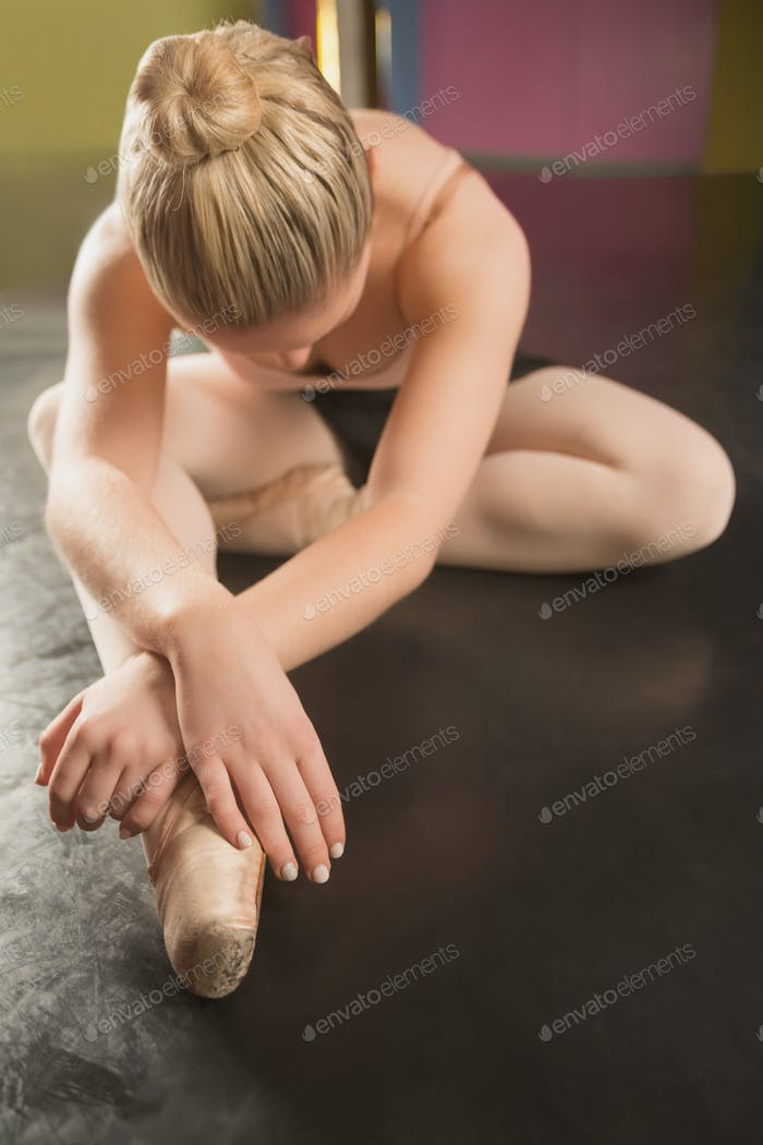 Ballerina sitting and bending forward in the ballet studio