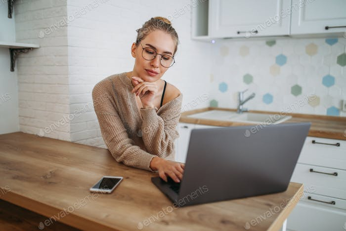 Beautiful smiling girl in glasses in knitted sweater using laptop at kitchen