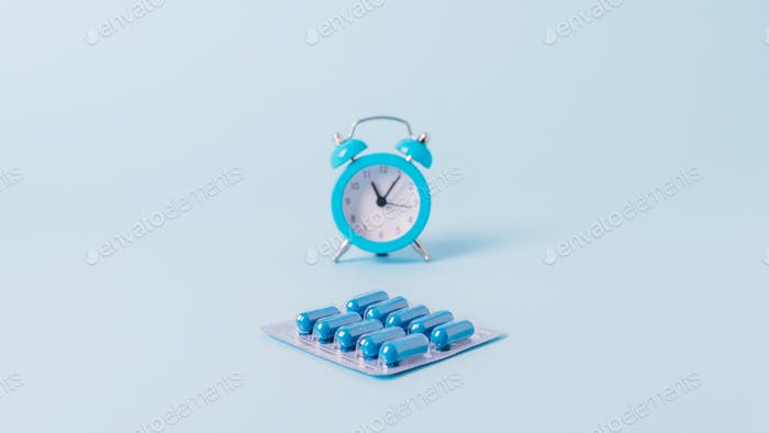 Pills, drugs work bedtime, schedule. Time to take medication. Blue alarm clock and medical blister