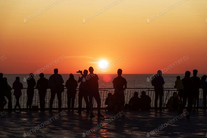 Silhouetten von Menschen gegen die untergehende Sonne an Deck eines Kreuzfahrtschiffes