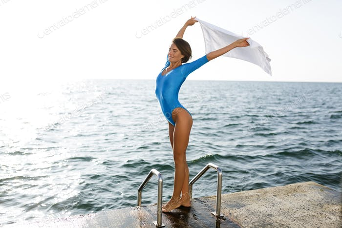 Portrait of lady with dark short hair standing and dreamily closing her eyes with sea on background