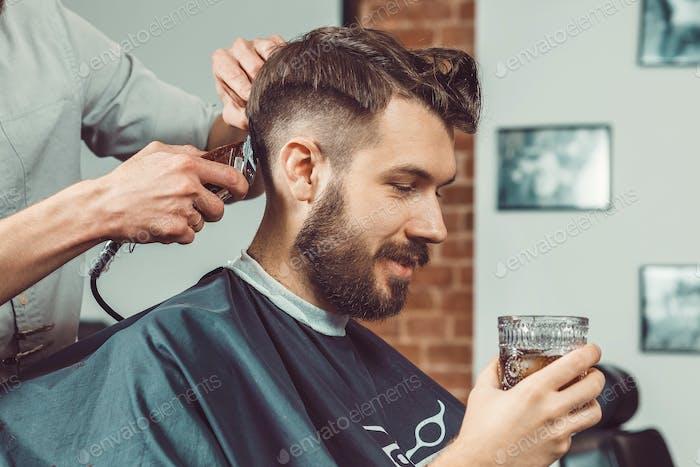 Die Hände des jungen Friseurs machen Haarschnitt zu attraktiven Mann im Friseurladen