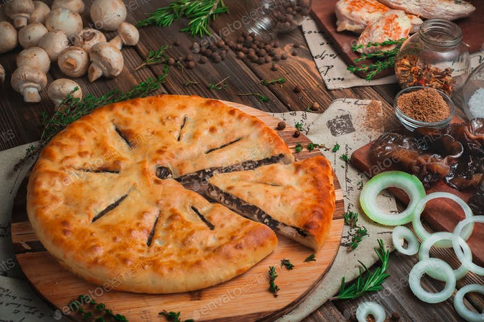 Homemade meat pie with chicken and mushrooms on a wooden background with ingredients. Traditional