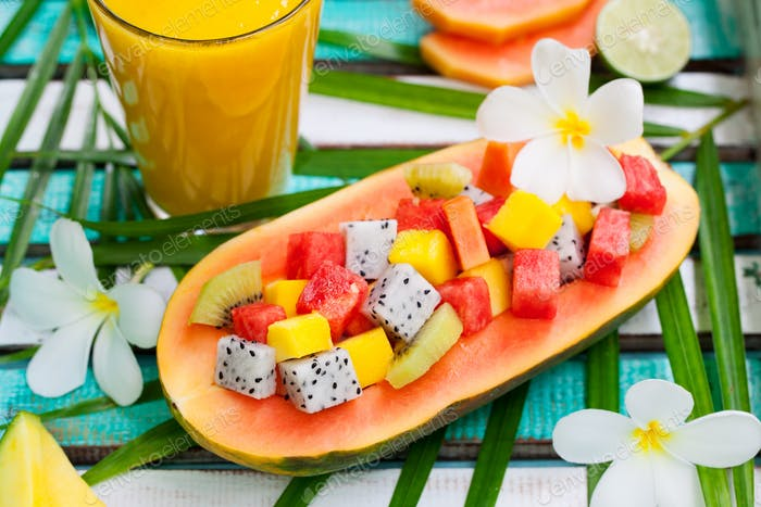 Tropical Fruit Salad in Half of Papaya with Mango Juice, Smoothie on Colorful Wooden Background.