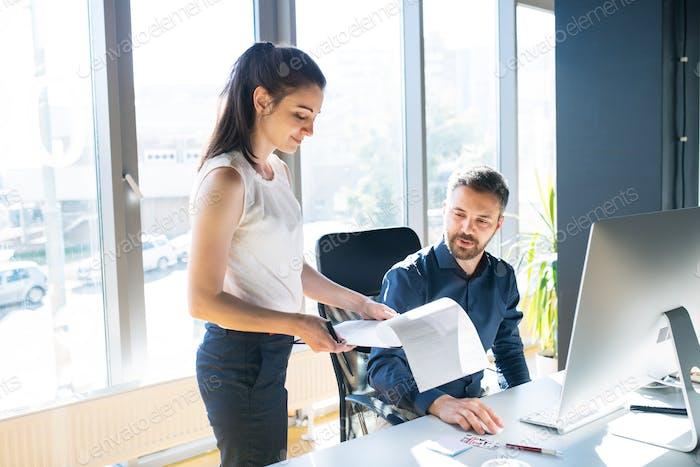 Zwei Geschäftsleute im Büro arbeiten zusammen.
