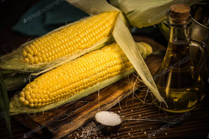 Whole corn on the cob on wooden board