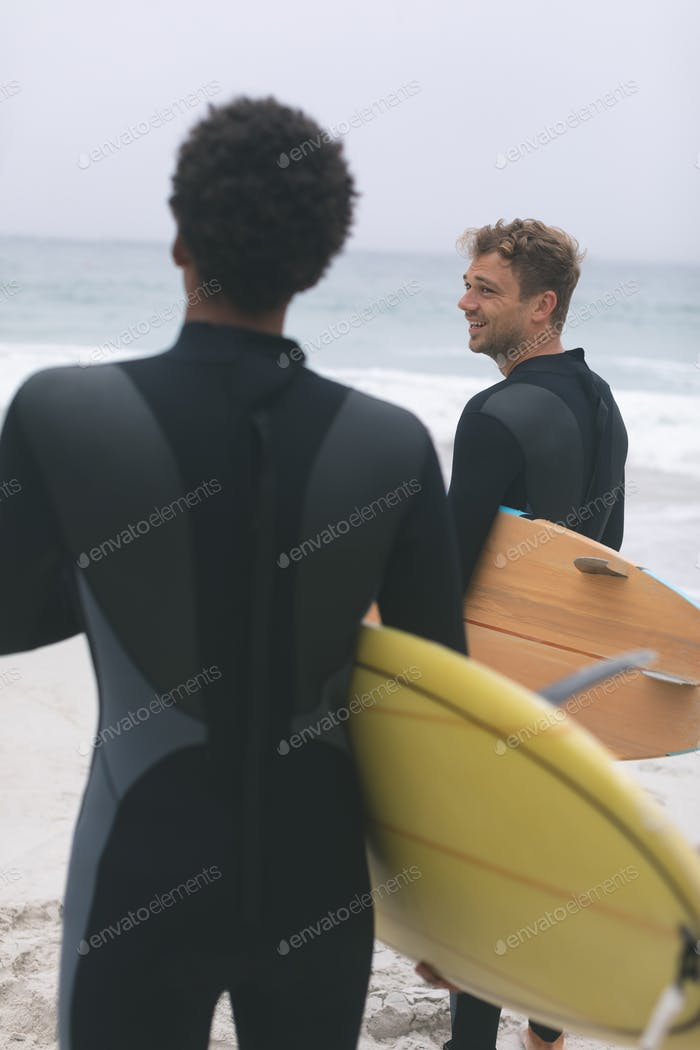 Young diverse male friends interacting with each other on beach while holding surfboards.