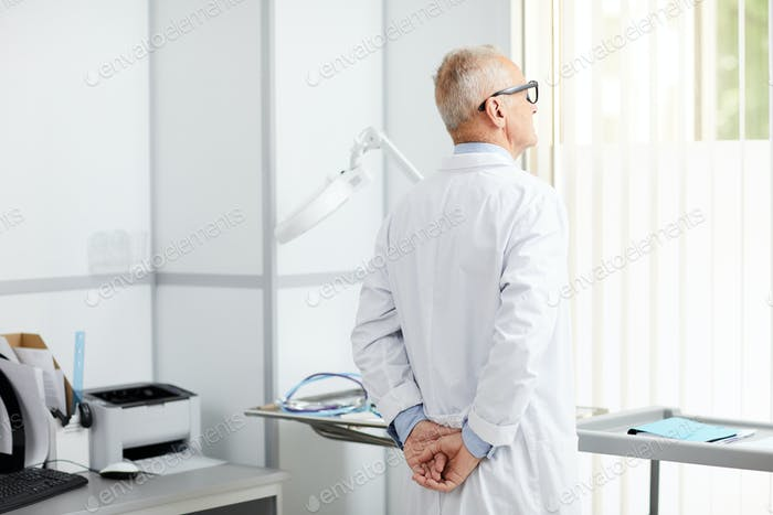 Pensive Senior Doctor by Window