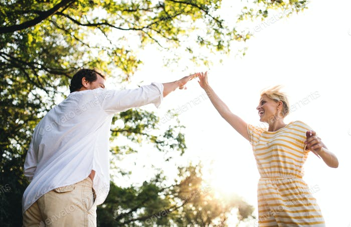 A young couple spending time together in nature in summer, making high five.