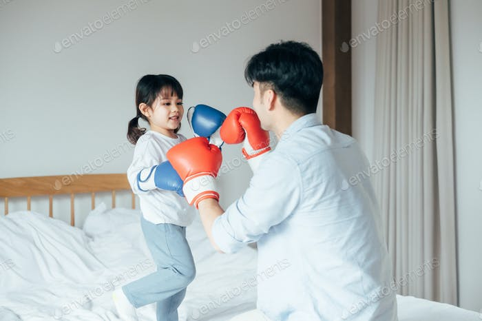Father and daughter boxing in bedroom