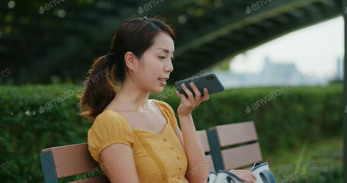 Woman send audio message on cellphone at outdoor
