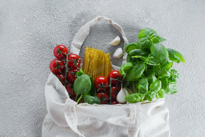 Reusable bag with groceries. Minimal waste. Basil, tomatoes cherry, garlic in fabric bag. Top view,