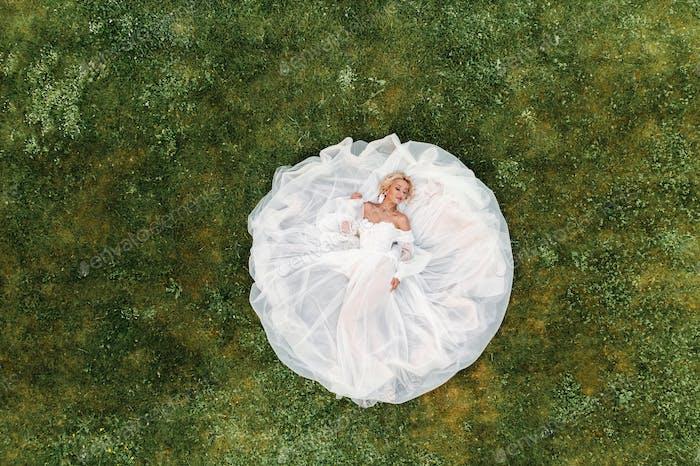Porträt einer schönen Braut auf dem Boden in einem weißen Hochzeitskleid liegen.Foto einer eleganten Braut