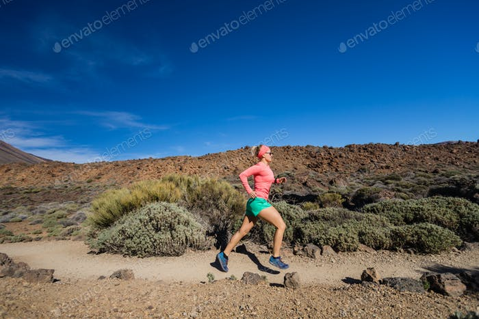 Trail running woman in mountains on sunny day