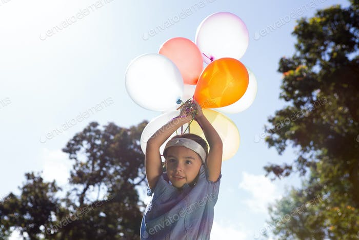 Happy little girl holding balloons on a sunny day