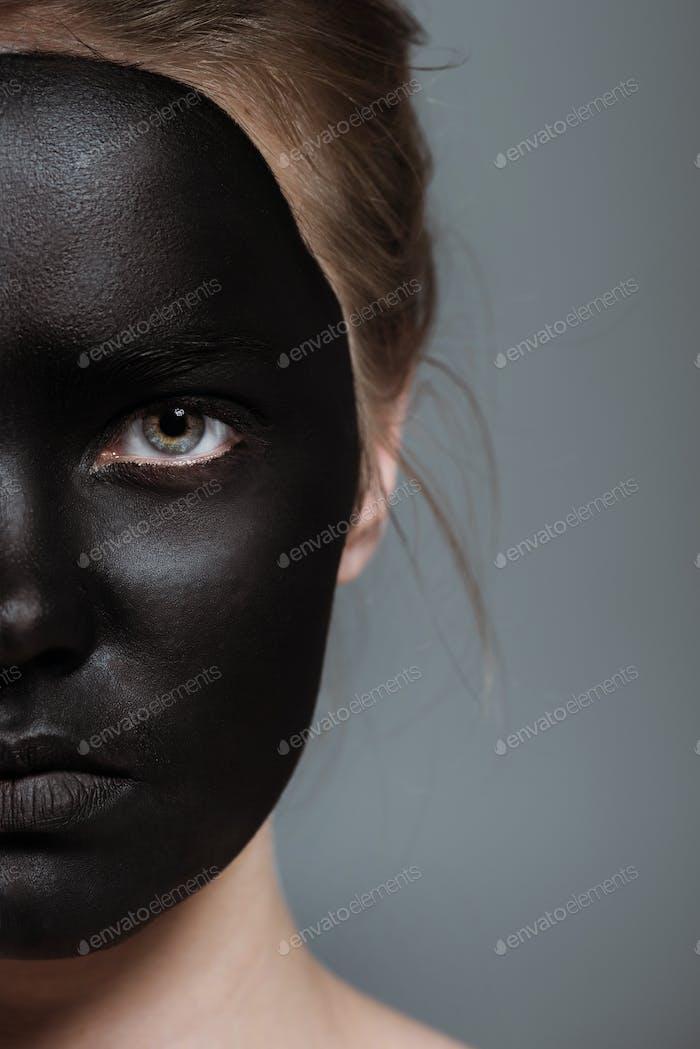 Beschnittene Ansicht von Mädchen mit kreativem schwarzen Bodyart auf Gesicht, isoliert auf Grau