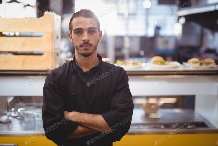 Portrait of confident young waiter standing against counter