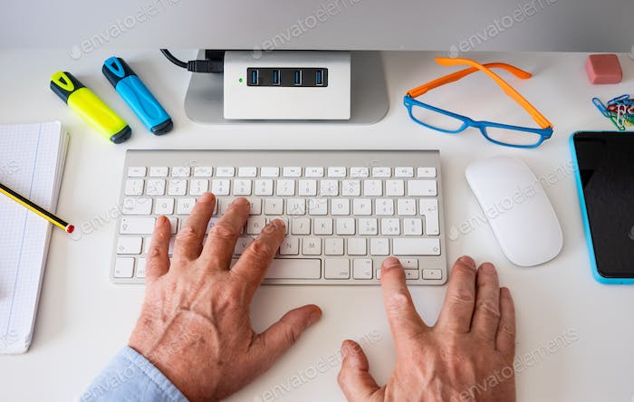 Male hands work on the computer keyboard - white desk