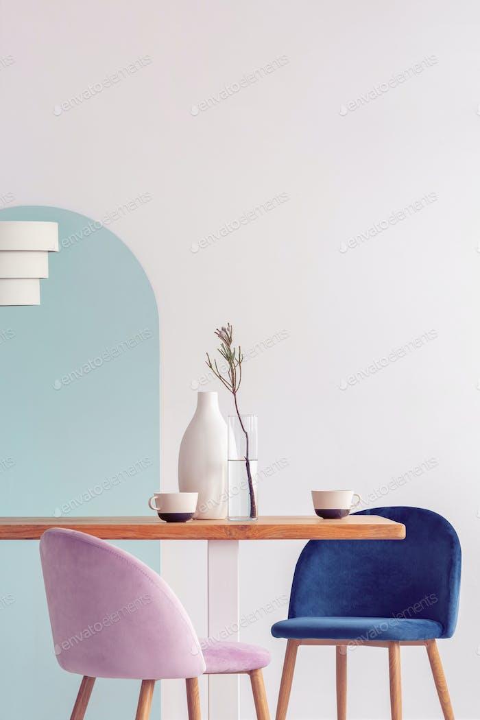 Stilvolle Pastellrosa und Petrolblau Stühle am langen Holztisch im hellen Esszimmer