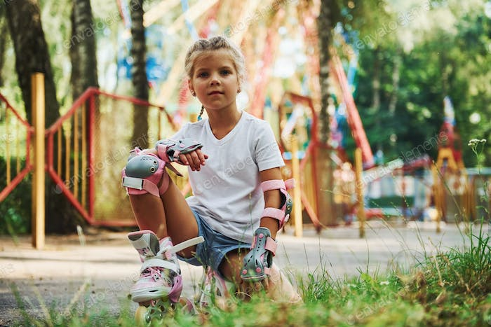 Cheerful little girl on roller skates have a good time in the park near attractions