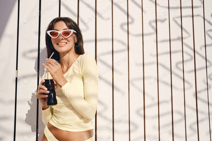 Smiling brunette girl in stylish swimwear and colorful sunglasses happily drinking soda on beach