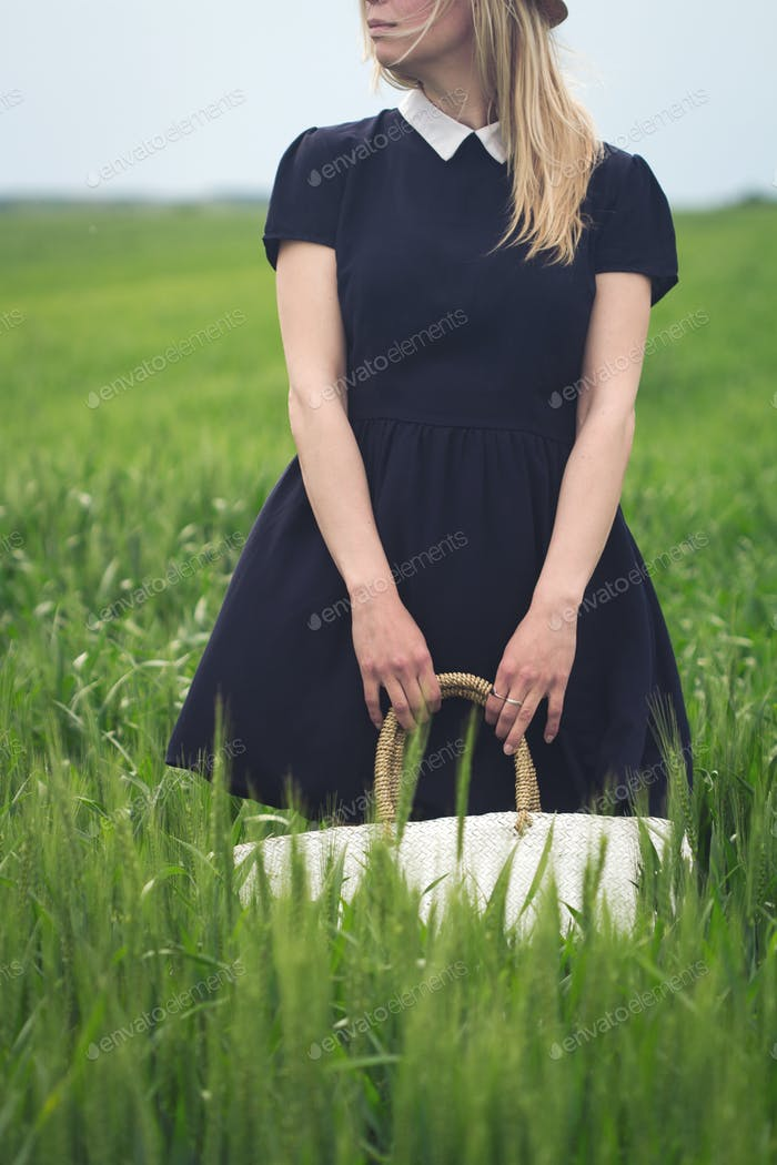 woman with black dress in a field of green wheat