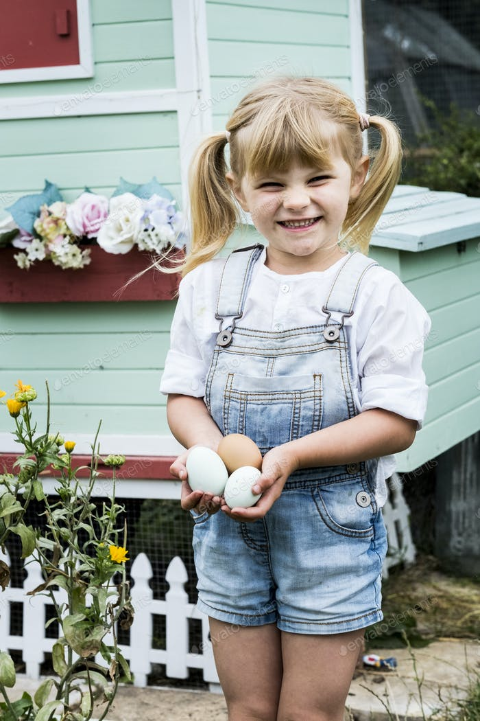 Blond girl standing in a garden in front of hen house, holding fresh eggs.