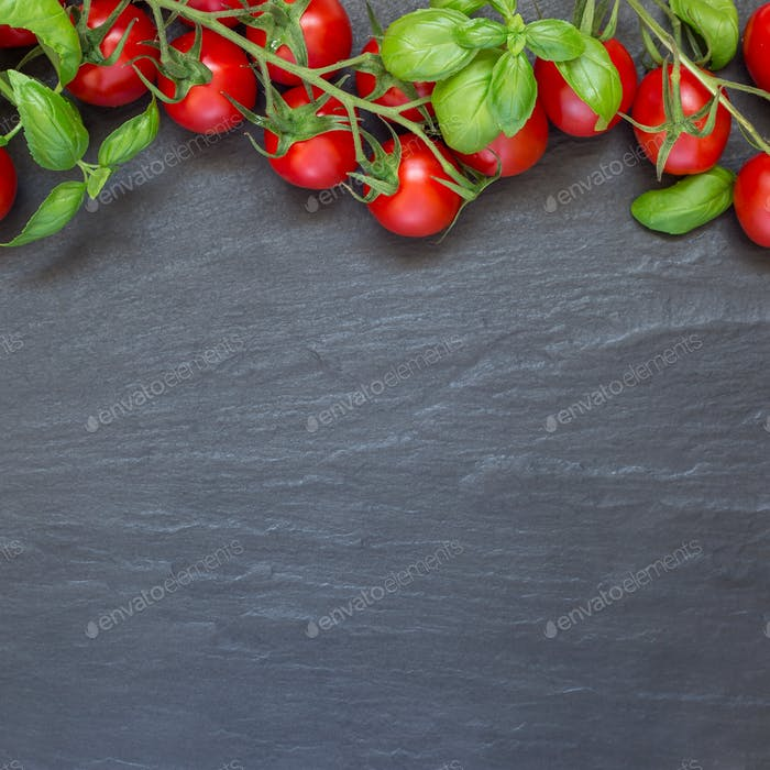 Cherry tomatoes with basil leaves on dark slate background, top
