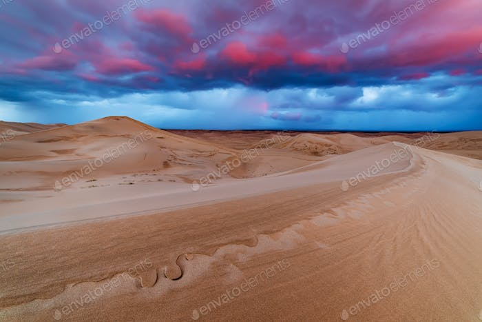 Dramatic sunset over sand dunes in the desert