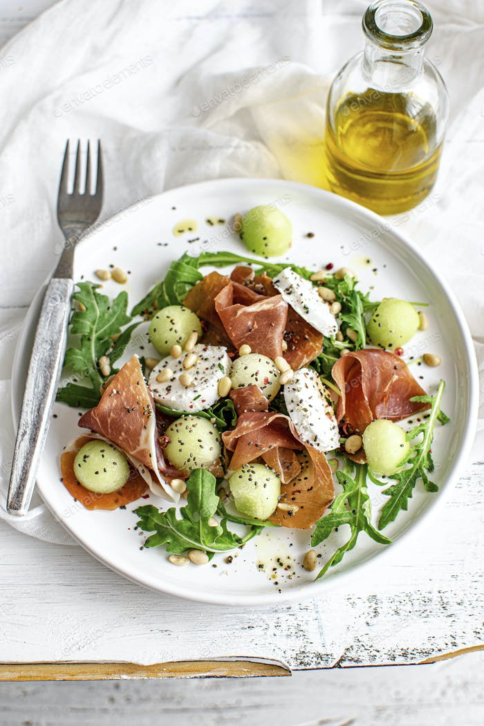 Colorful summer salad bowl with parma ham