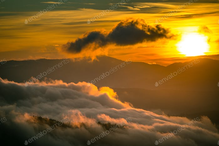 Bright sun setting behind mountains with dramatic sky on background