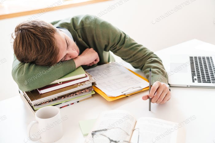 Student at the table indoors sleeping on books.
