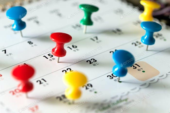 Thumb tack pins on calendar as reminder