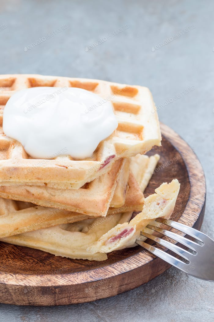 Homemade savory belgian waffles with bacon and shredded cheese on wooden plate, vertical, copy space