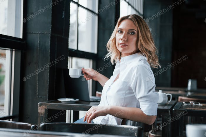 Taking cup of coffee. Businesswoman with curly blonde hair indoors in cafe at daytime