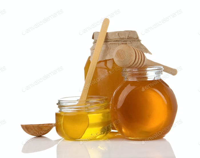 glass pot of honey, spoon and stick