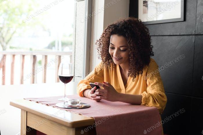 Frau mit Smartphone im Restaurant