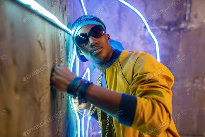 Black rapper in underpass neon light on background