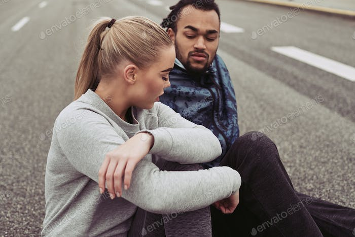 Diverse young couple taking a break from an outdoor run