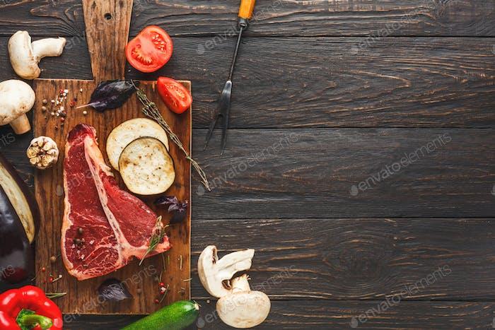 Rohes T-Bone-Steak auf Holzbrett